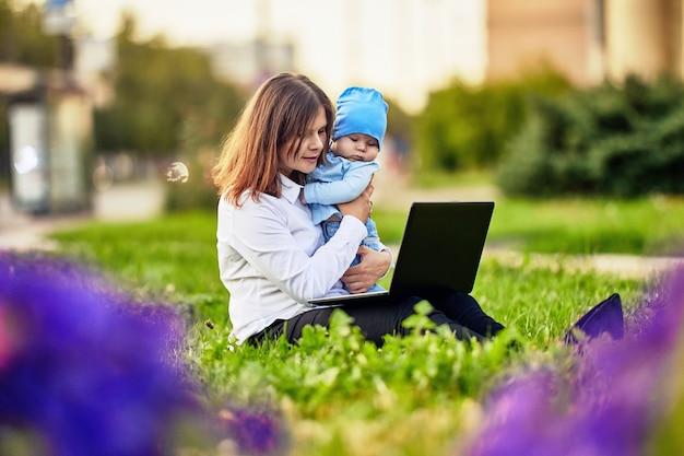 Vrouw met zwangerschapsverlof werkt op afstand online buiten zit voor laptop met baby in haar armen