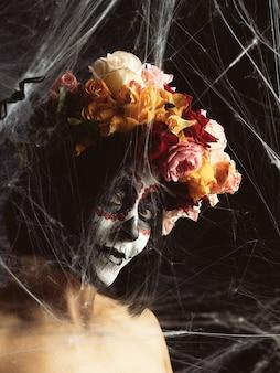 Vrouw met zwart haar is gekleed in een krans van veelkleurige rozen en make-up wordt gemaakt op haar gezicht suikerschedel tot de dag van de doden