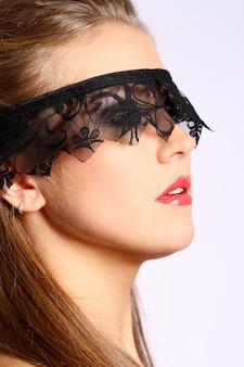 Vrouw met zwart kantmasker over haar gezicht