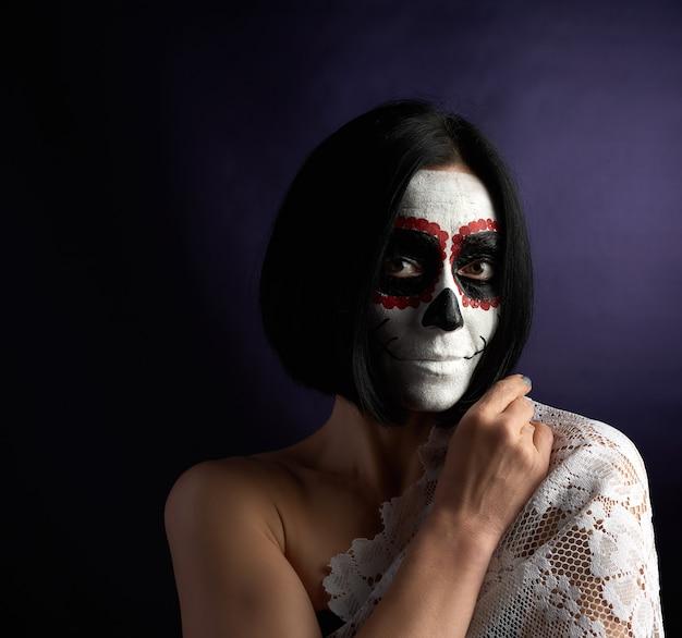 Vrouw met zwart kort haar in witte make-up suiker hoofd naar de dag van de doden