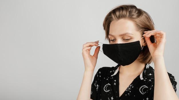 Vrouw met zwart overhemd en masker