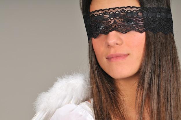 Vrouw met zwarte kanten blinddoek en witte engelenvleugels achter haar rug vormt met gevouwen armen op grijze muur