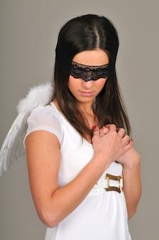 Vrouw met zwarte kanten blinddoek en witte engelenvleugels achter haar rug vormt met gevouwen armen