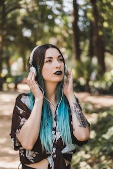 Vrouw met zwarte lippenstift het luisteren muziek op hoofdtelefoon in het park