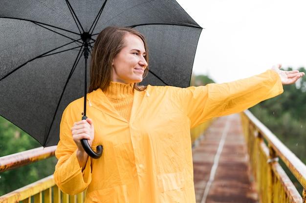 Vrouw met zwarte paraplu die haar hand toeneemt