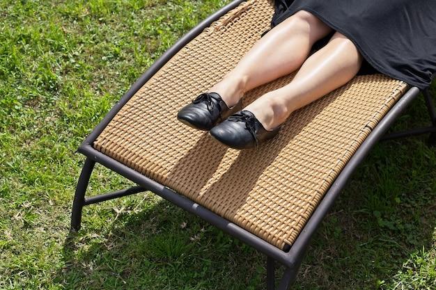 Vrouw met zwarte schoenen en een zwarte jurk zittend onder het zonlicht