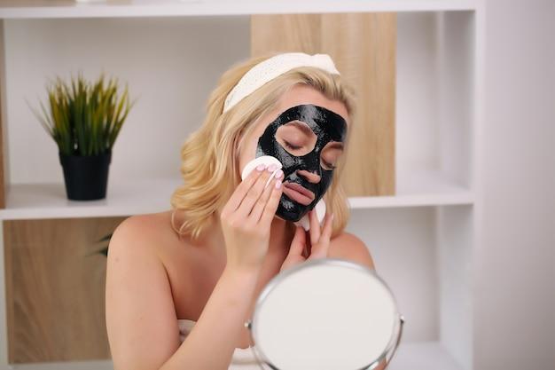 Vrouw met zwarte schoonmaak zwarte houtskool masker op haar gezicht.