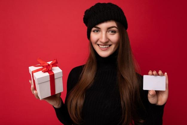 Vrouw met zwarte trui en hoed geïsoleerd op rode achtergrond met creditcard en geschenkdoos camera kijken.