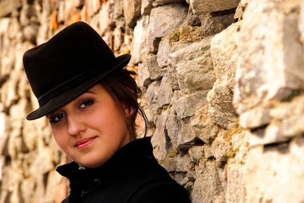 Vrouw met zwarte vilthoed leunend tegen de stenen muur