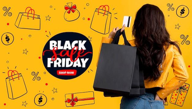 Vrouw met zwarte vrijdag boodschappentassen