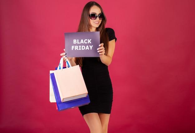 Vrouw met zwarte vrijdag inscriptie en boodschappentassen