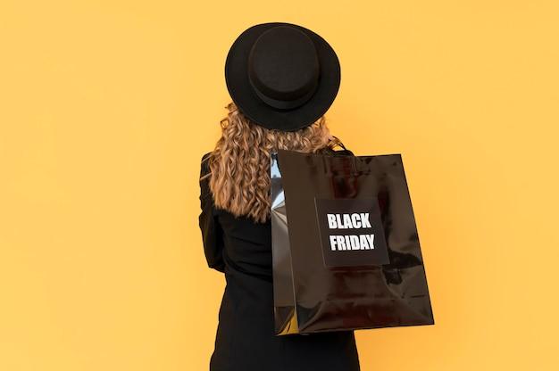 Vrouw met zwarte vrijdagzak van achter schot