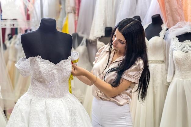Vrouw meten trouwjurk op mannequin in salon in