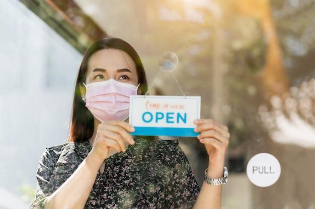 Vrouw mkb-ondernemer opent coffeeshop en eten, nadat de regering quarantainemaatregelen heeft versoepeld om epidemie te voorkomen.