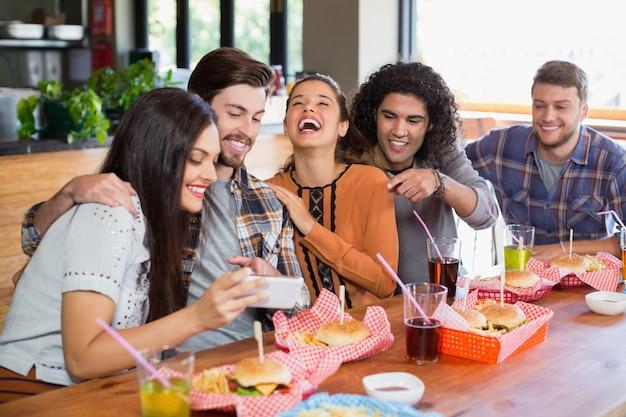 Vrouw mobiel tonen aan vrolijke vrienden in restaurant
