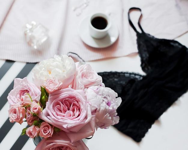 Vrouw mode-accessoires, ondergoed, boeket rozen en pionen, parfum, sieraden, koffie