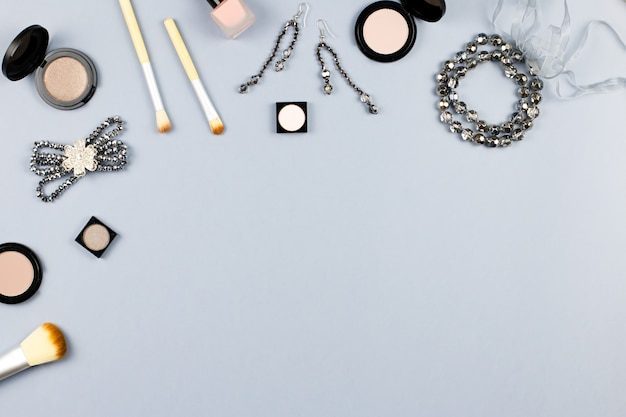 Vrouw mode accessoires, sieraden en cosmetica op stijlvolle grijze achtergrond. plat leggen