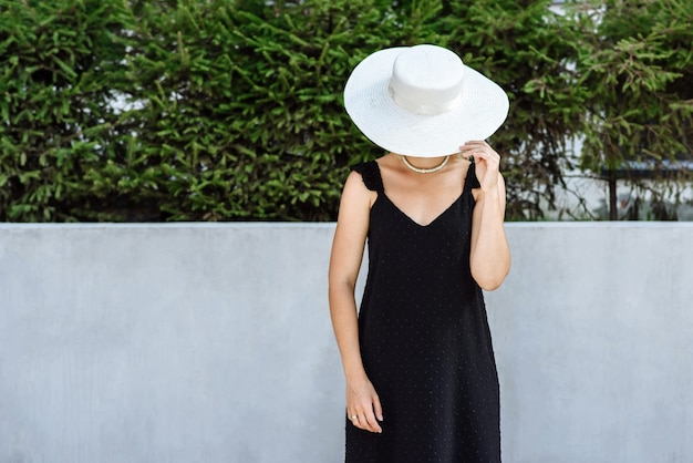 Vrouw model in hoed en zwarte jurk poseren op de achtergrond van de stad straat in nieuwe kleding catalogus