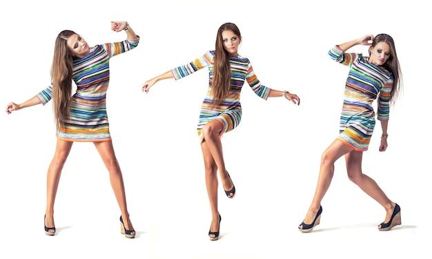 Vrouw model in korte jurk in volle lengte in studio op witte muur in verschillende poses
