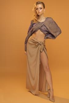 Vrouw model poseren in studio, vrouw in stijlvolle modieuze kleding rok en blouse met wijde mouwen. hoge kwaliteit foto