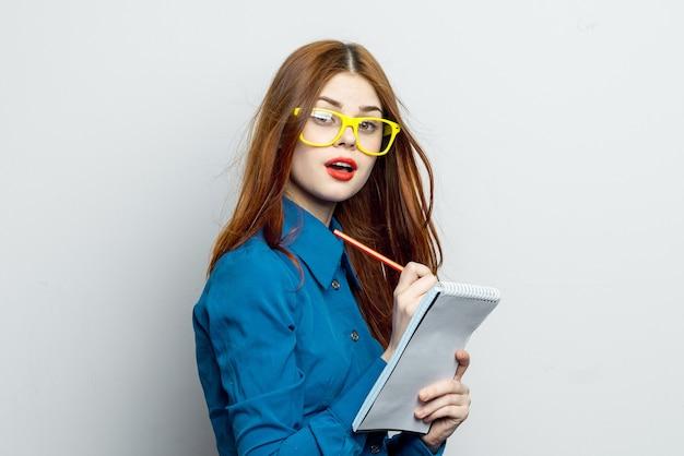 Vrouw model poseren met bril, emoties met een notitieboekje in haar handen