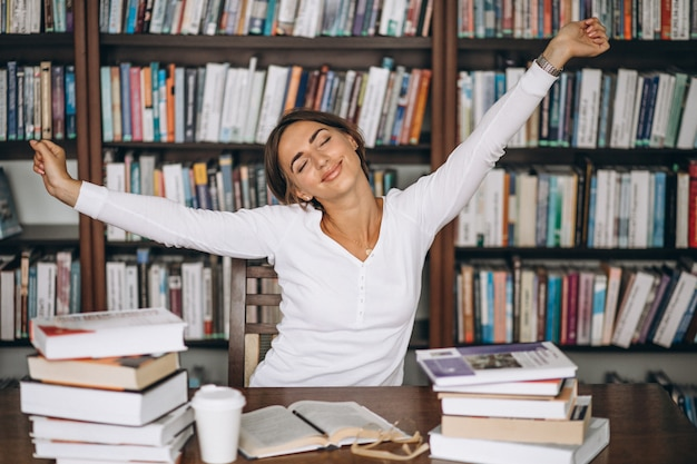 Vrouw moe die zich uitstrekt in de bibliotheek