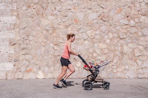 Vrouw, moeder die geschiktheid doet die de babywandelwagen duwt.