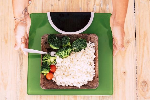 Vrouw moet kiezen tussen een gezond leven of niet om een goede, gezonde en geweldige levensstijl te hebben en om gelukkig te zijn met zichzelf - man kiest welk soort voedsel het liefste heeft - er zijn groenten op een weegschaal