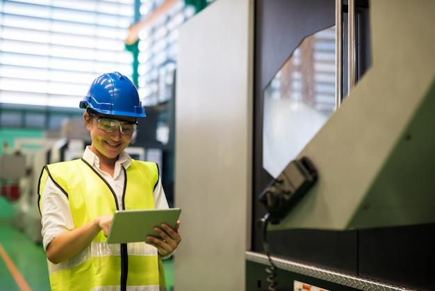 Vrouw monitor fabriek machine door tablet