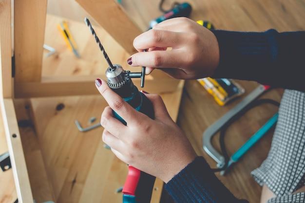 Vrouw montage houten meubelen, vaststelling of reparatie van huis