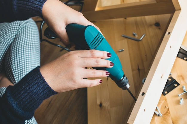 Vrouw montage houten meubels, vaststelling of reparatie van huis met boorgereedschap.