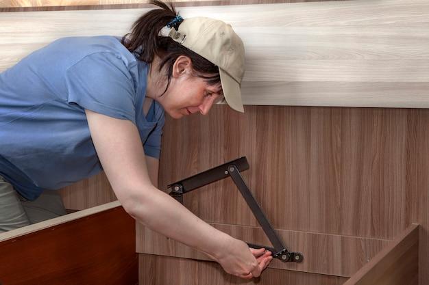 Vrouw monteert slaapmeubilair, stalen scharnieren hefmechanisme vastgeschroefd aan frame.