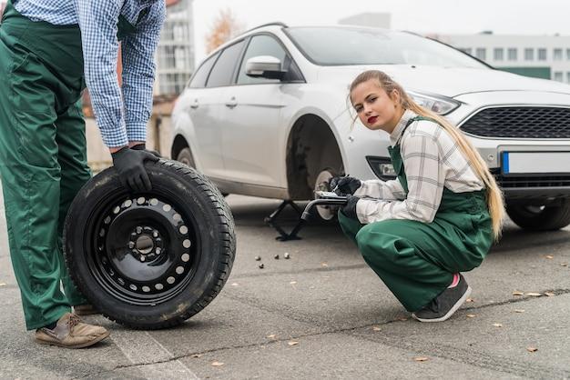 Vrouw monteur controleren reservewiel in de buurt van auto