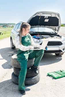 Vrouw monteur met kapotte auto en laptop