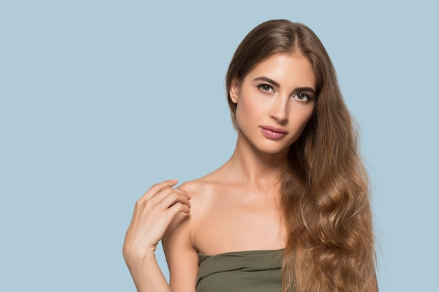 Vrouw mooi gezicht gezond. schoonheid jong model zichzelf aan te raken. kleur achtergrond. blauw