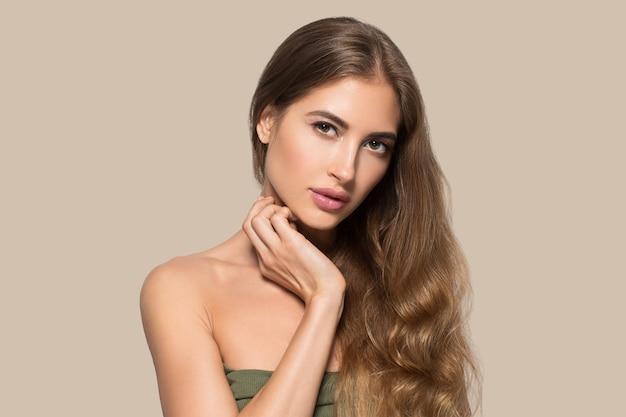 Vrouw mooi gezicht gezond. schoonheid jong model zichzelf aan te raken. kleur achtergrond. bruin