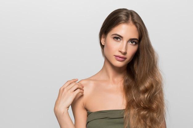 Vrouw mooi gezicht gezond. schoonheid jong model zichzelf aan te raken. kleur achtergrond. grijs