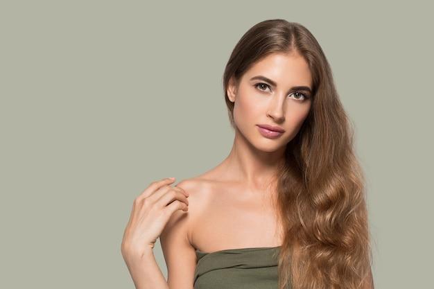 Vrouw mooi gezicht gezond. schoonheid jong model zichzelf aan te raken. kleur achtergrond. groente