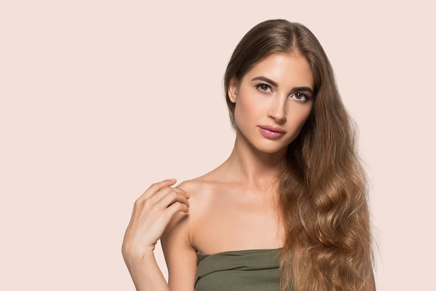 Vrouw mooi gezicht gezond. schoonheid jong model zichzelf aan te raken. kleur achtergrond. roze