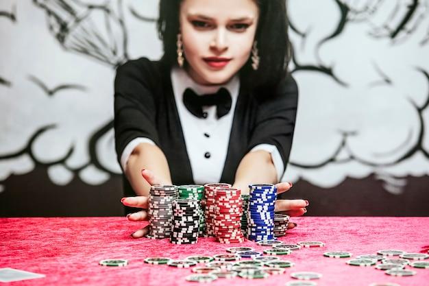 Vrouw mooie jonge succesvolle gokken in een casino aan een tafel met kaarten, chips en alcohol close-up
