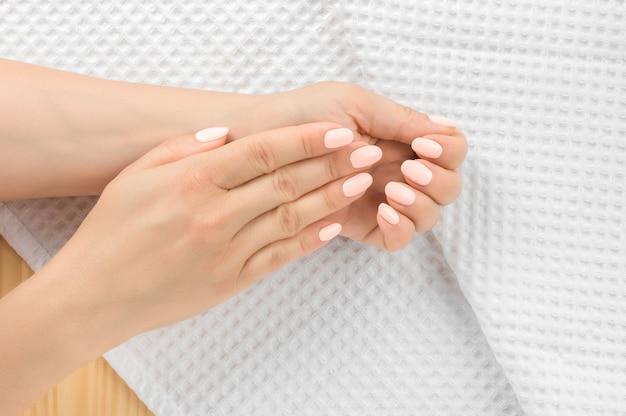 Vrouw mooie nagelverzorging op handdoek. perfecte kunstmatige vingernagels van jonge vrouw. gemanicuurde nagels en zachte handen huid. schoonheidsbehandeling. witte handdoek achtergrond