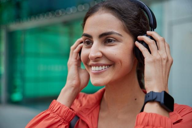 Vrouw motiveert om te sporten bereidt zich voor op training buitenshuis zet koptelefoon op draagt armband om resultaten bij te houden keert terug naar sportieve levensstijl na ziekte klaar voor ochtendtraining