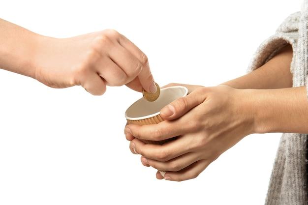 Vrouw munt aanbrengend beker in handen van vrouwelijke bedelaar, geïsoleerd op wit