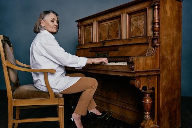 Vrouw muziekleraar zittend in de buurt van de piano