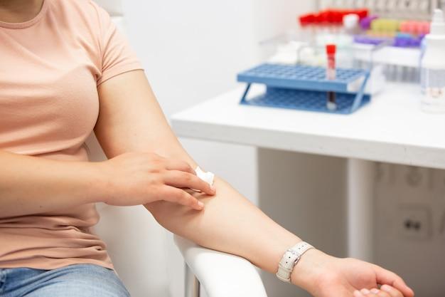 Vrouw na het nemen van een bloed uit een ader, medisch concept