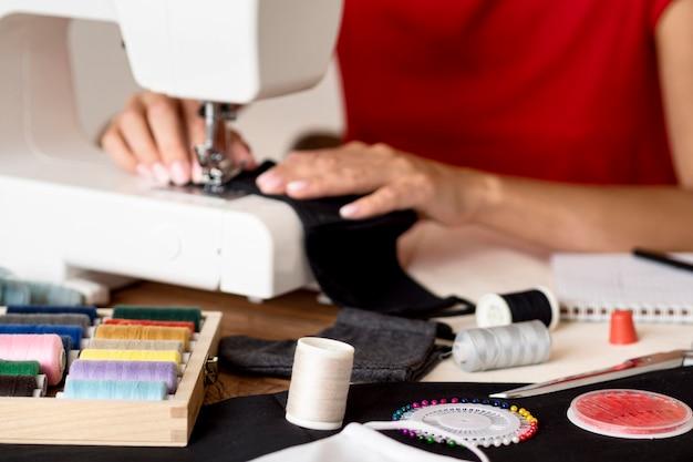 Vrouw naaien gezichtsmasker met draad