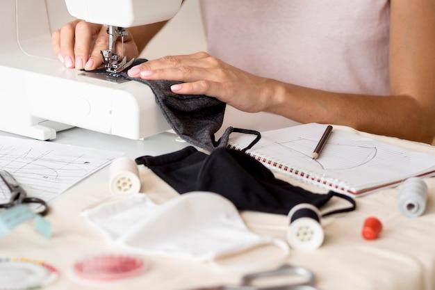 Vrouw naaien gezichtsmasker met laptop