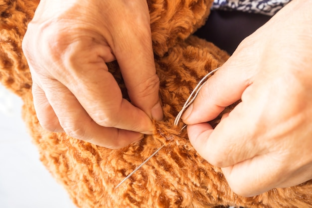Vrouw naaiende teddybeer, vernieuw een gebroken pop.