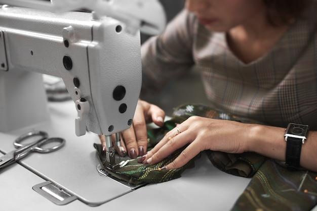 Vrouw naaister bezig met moderne elektrische naaimachine
