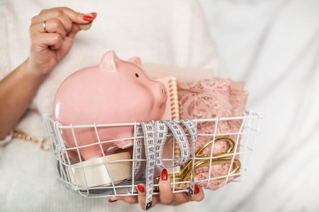 Vrouw naaister met gevouwen kantstof, schaar, meetlint en spaarvarken in gaasmand. besparing, zuinigheid in het knippen en naaien van dameskleding en sociaal-economisch concept.